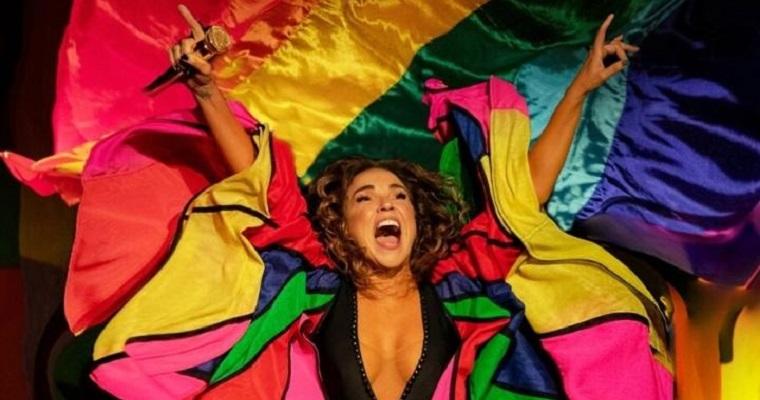 Daniela Mercury sorrindo com roupas coloridas.